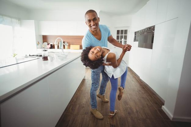 幸せなカップルが台所で踊るとカメラを見て