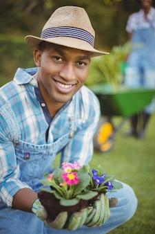 花を持って庭で身をかがめるハンサムな男
