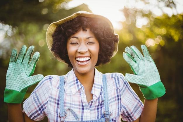 庭で彼女の園芸用手袋を見せて幸せな女
