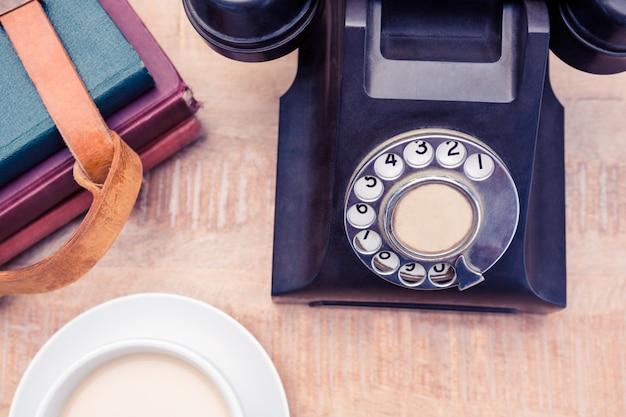 Высокий угол обзора старого стационарного телефона с дневниками и кофе на столе