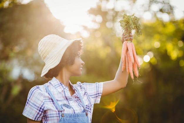 庭でニンジンを保持している女性の笑みを浮かべてください。