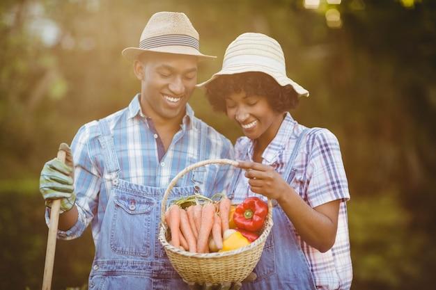 野菜のバスケットを見て庭で笑顔のカップル