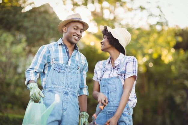 水まき缶を保持している笑顔のカップルと庭の園芸鋏