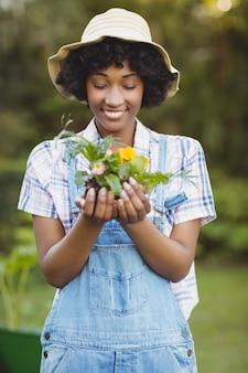 Улыбающиеся женщина с цветами в саду
