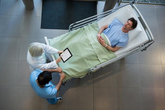 Врачи обсуждают над цифровым планшетом в коридоре, а пациент лежит на аварийных носилках