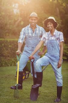 シャベルと庭で熊手を持って笑顔のカップル