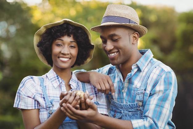 庭でジャガイモを持って笑顔のカップル