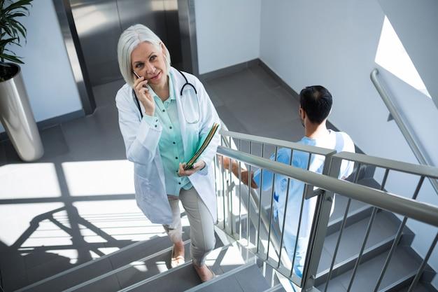 Доктор разговаривает по мобильному телефону во время прогулки по лестнице