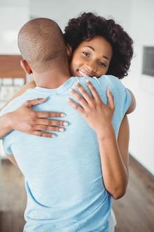 幸せなカップルが台所で抱きしめる