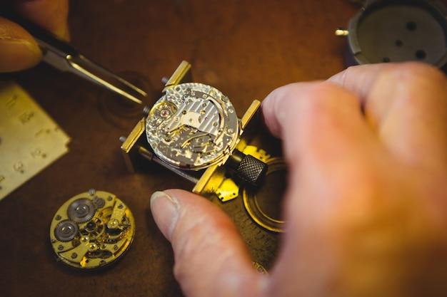 Часовщик ремонтирует часы