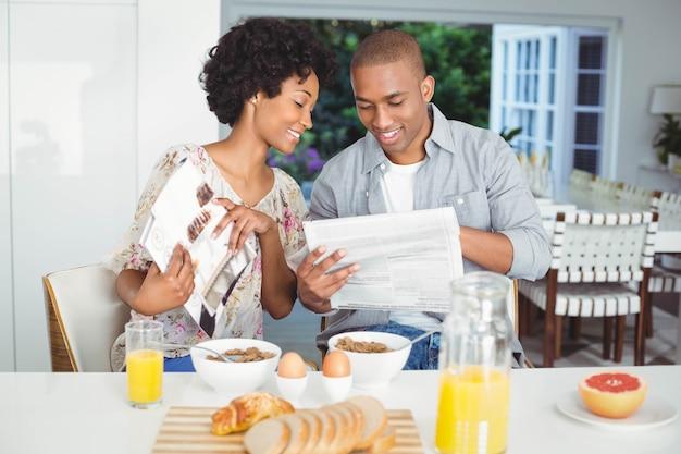 Улыбаясь пара читает журнал и документы во время завтрака на кухне