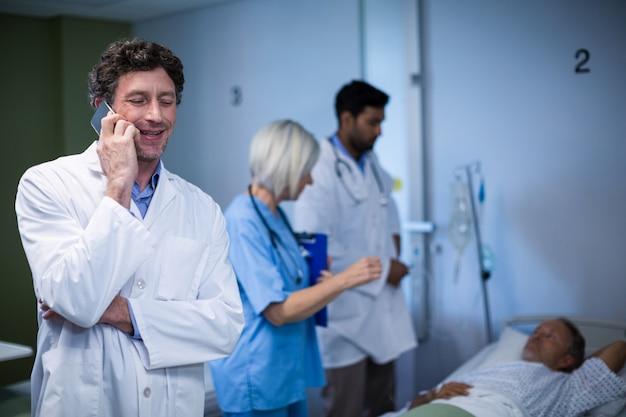 Доктор разговаривает по мобильному телефону в больнице