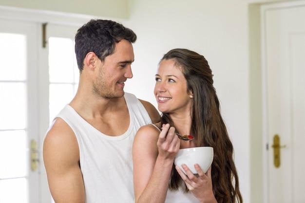 若いカップルが台所で一緒に朝食をとりながら笑顔