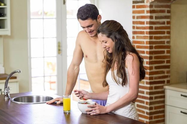 Молодая пара стоит возле кухонной столешницы и завтракает вместе