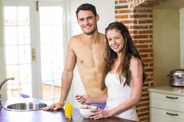 Портрет молодой пары, стоя возле столешницы на кухне и завтракают вместе