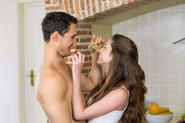 Молодая пара кормит фрукты друг другу на кухне