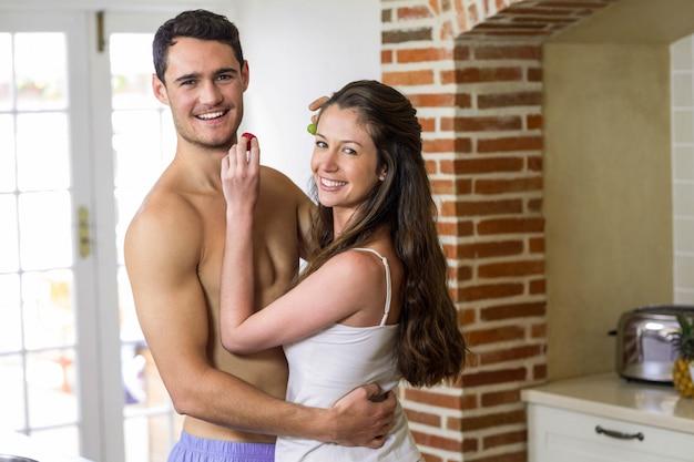 Портрет молодой пары, кормления фрукты друг другу на кухне