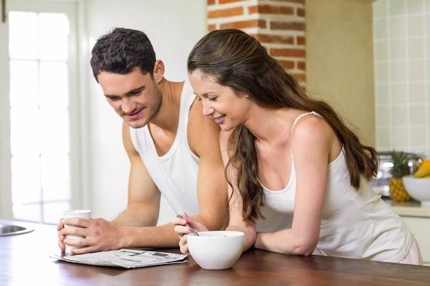 Молодая пара читает газету во время завтрака на кухне