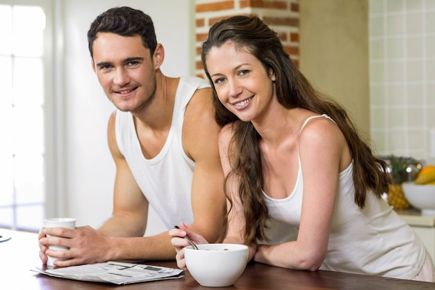 Портрет молодой пары, читая газету во время завтрака на кухне