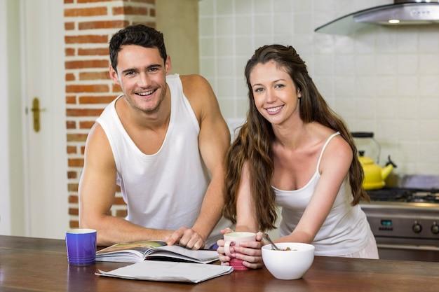 Портрет молодой пары, стоя возле столешницы и проверка их персональный органайзер в первой половине дня