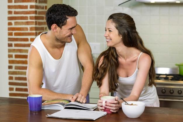 Молодая пара, глядя друг на друга, стоя возле кухонной столешницы