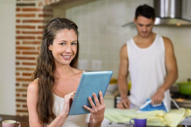 Портрет женщины с помощью планшета в кухне, а мужчина гладит рубашку в фоновом режиме