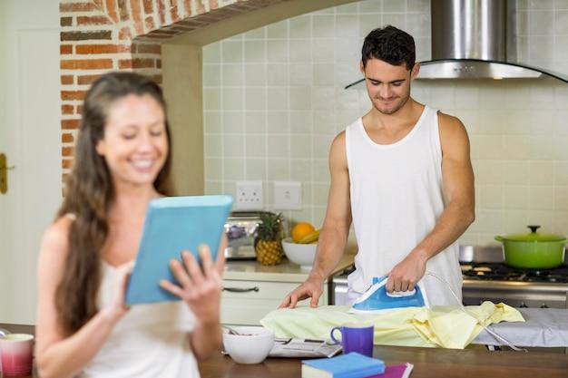 Мужчина гладит рубашку и женщину с помощью планшета на кухне