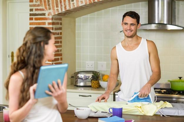 Мужчина разговаривает с женщиной во время глажения рубашки на кухне