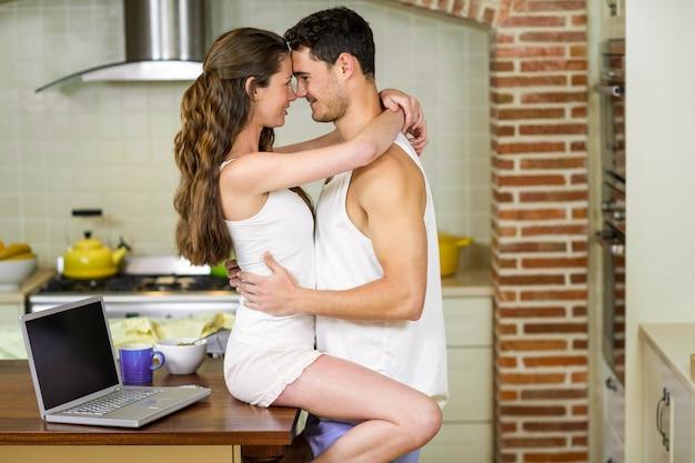 Романтическая молодая пара обнимаются на кухне