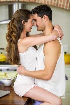 Крупный план романтичной молодой пары обнимаются на столешнице кухни