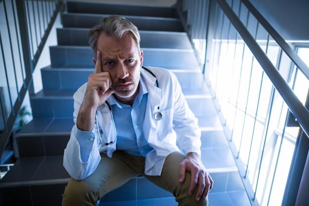 階段に座っている悲しい医師の肖像画