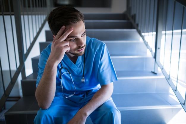緊張した男性看護師が階段の上に座って