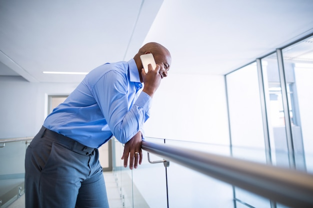 Доктор разговаривает по мобильному телефону в коридоре