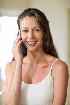 台所で携帯電話で話している若い女性の肖像画