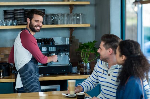 コーヒーショップでウェイターと対話する顧客