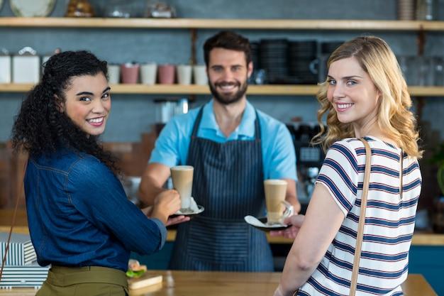 カウンターで顧客にコーヒーのカップを提供するウェイター
