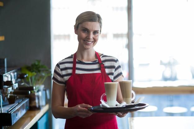 カフェのカウンターで冷たいコーヒーのカップを保持しているウェイトレスの笑顔