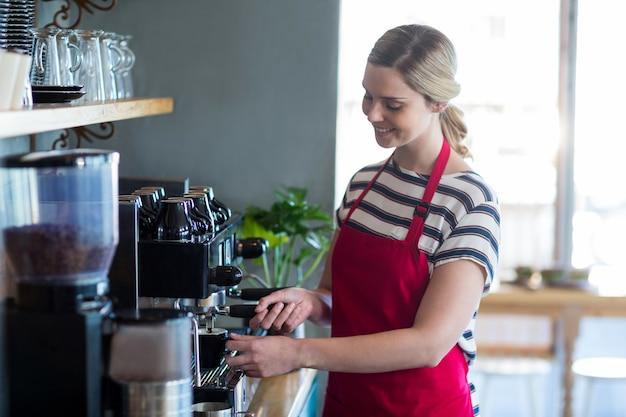 コーヒーショップで一杯のコーヒーを作るウェイトレス