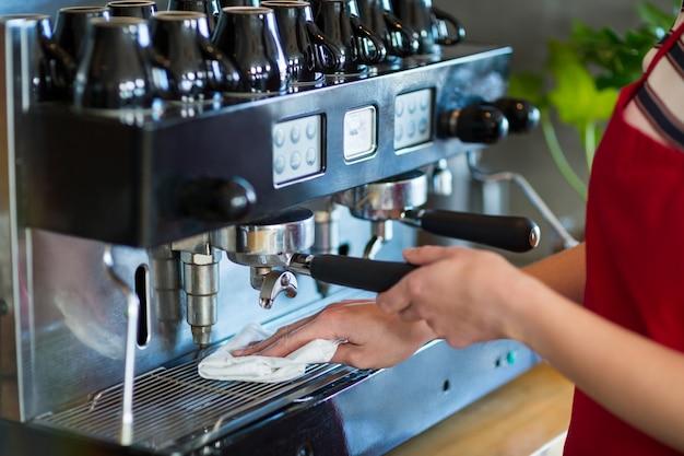 Официантка, вытирающая эспрессо-машину салфеткой в кафе