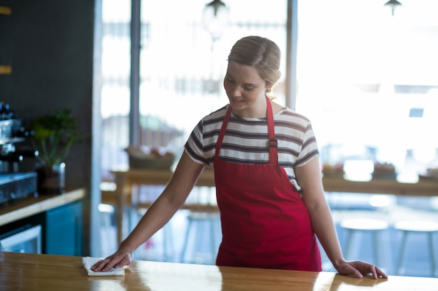 Официантка вытирает стол у стойки
