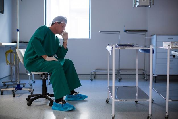 病棟に座っている緊張した男性外科医