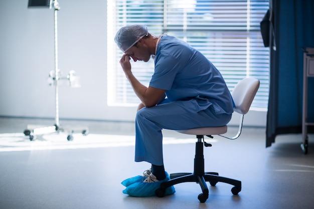 廊下に座っている緊張した男性看護師