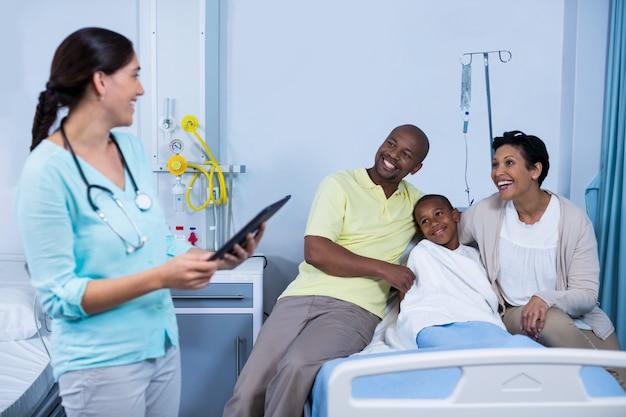 Доктор используя цифровую таблетку пока родители взаимодействуя с пациентом