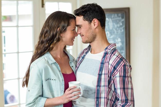幸せな若いカップルお互いを受け入れて、リビングルームで一杯のコーヒーを飲んで