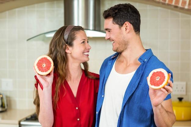 幸せなカップルの台所でブラッドオレンジのスライスを保持