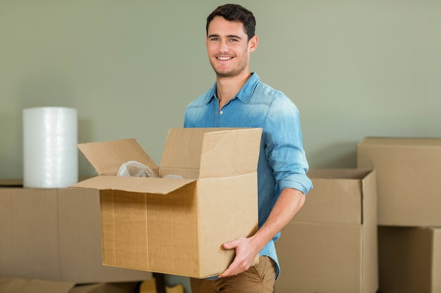若い男が彼の新しい家でカートンボックスを運ぶ