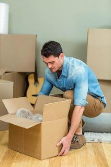 若い男が彼の新しい家の家でカートンボックスを運ぶ
