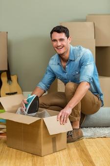 若い男が彼の新しい家で箱を開梱
