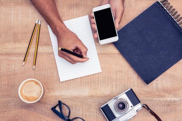 カメラと眼鏡のテーブルでスマートフォンを押しながらメモ帳に書いて実業家のオーバーヘッドビュー