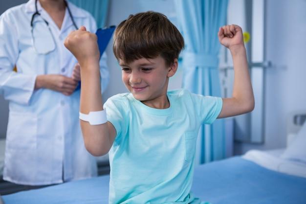 彼の筋肉が屈曲し、バックグラウンドで立っている女性医師の少年